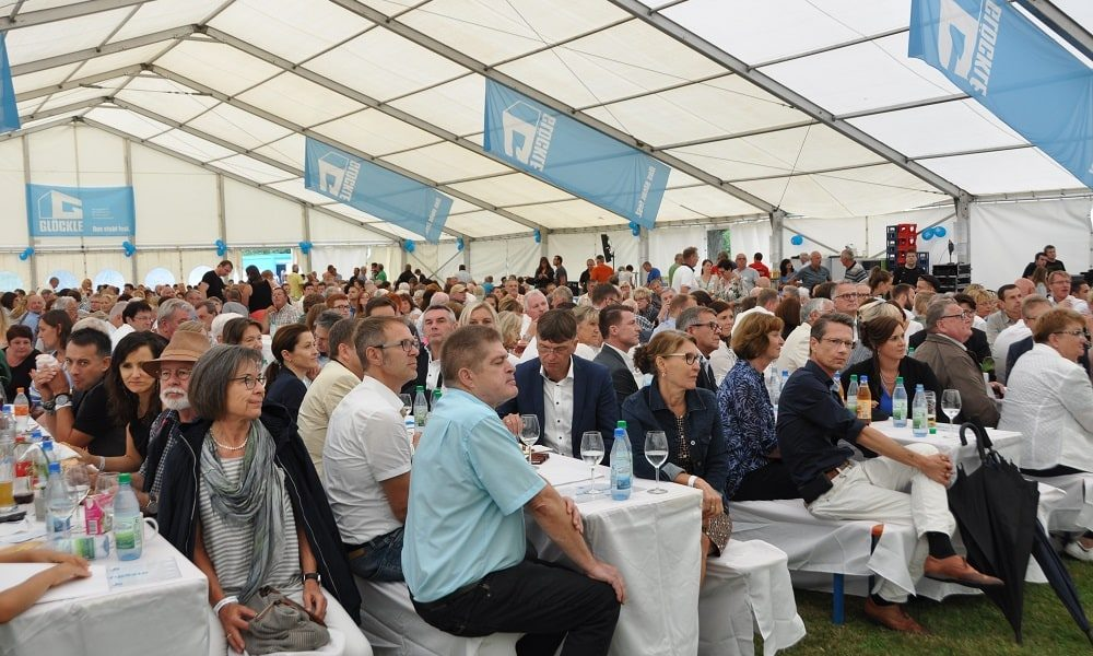 Glöckle-Mitarbeiter und Gäste sitzen im geschmückten Festzelt