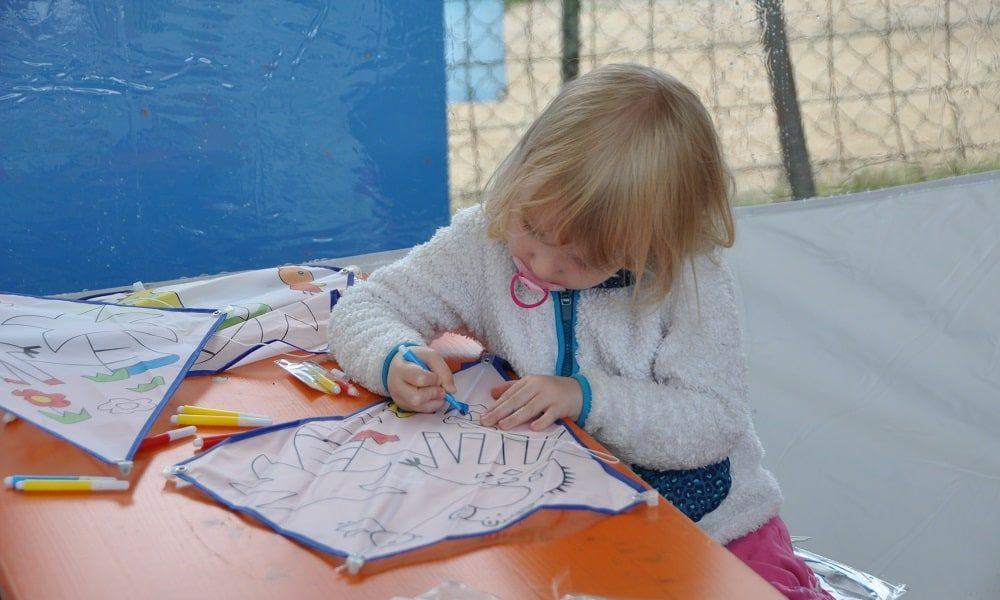 Kind malt einen Spieldrachen in der Kinderecke vom Glöckle Jubiläumsfest aus