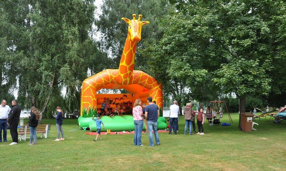 Kinder spielen auf einer großen Hüpfburg beim Jubiläumsfest
