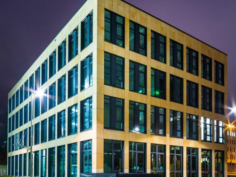 Bürogebäude mit Natursteinfassade bei Nacht