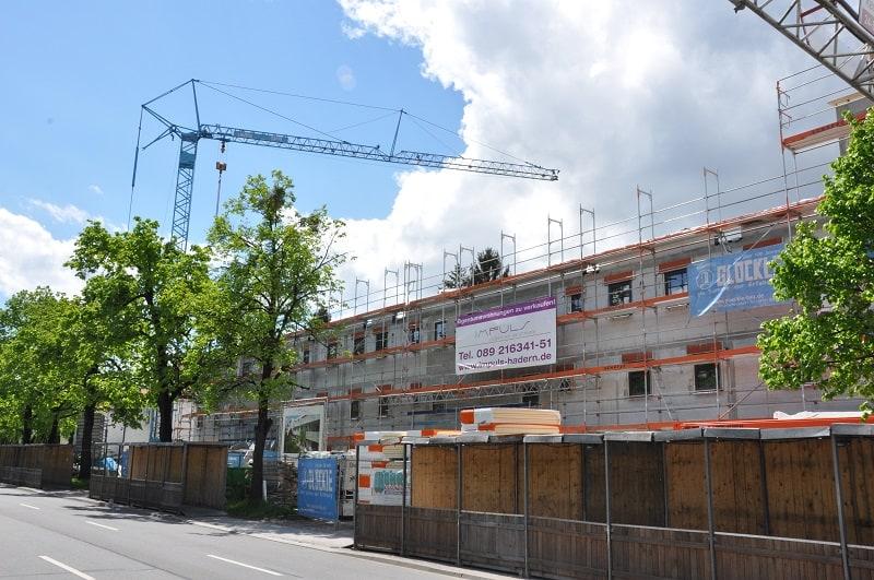 Blauer Glöckle-Baukran ragt über dem Rohbau der neuen Wohnanlage in Nürnberg