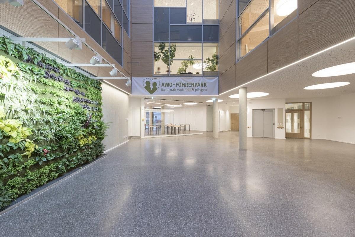 Freundlich und modern gestalteter mit Pflanzen an den Wänden Foyerbereich des neuen Seniorenwohnens am Föhrenpark