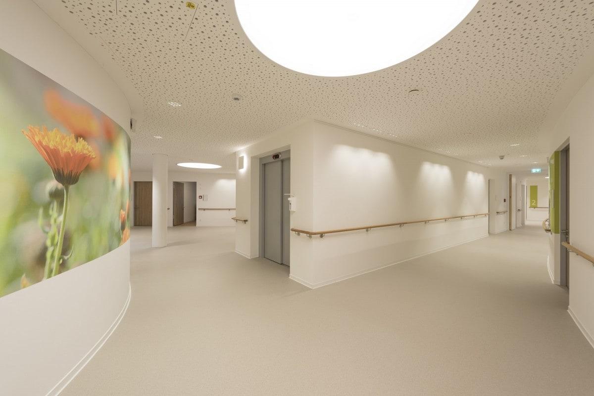 Helle, moderne Gänge mit großen Deckenlichtern und freundlichen Bilder prägen den Neubau des Seniorenwohnen am Föhrenpark in München