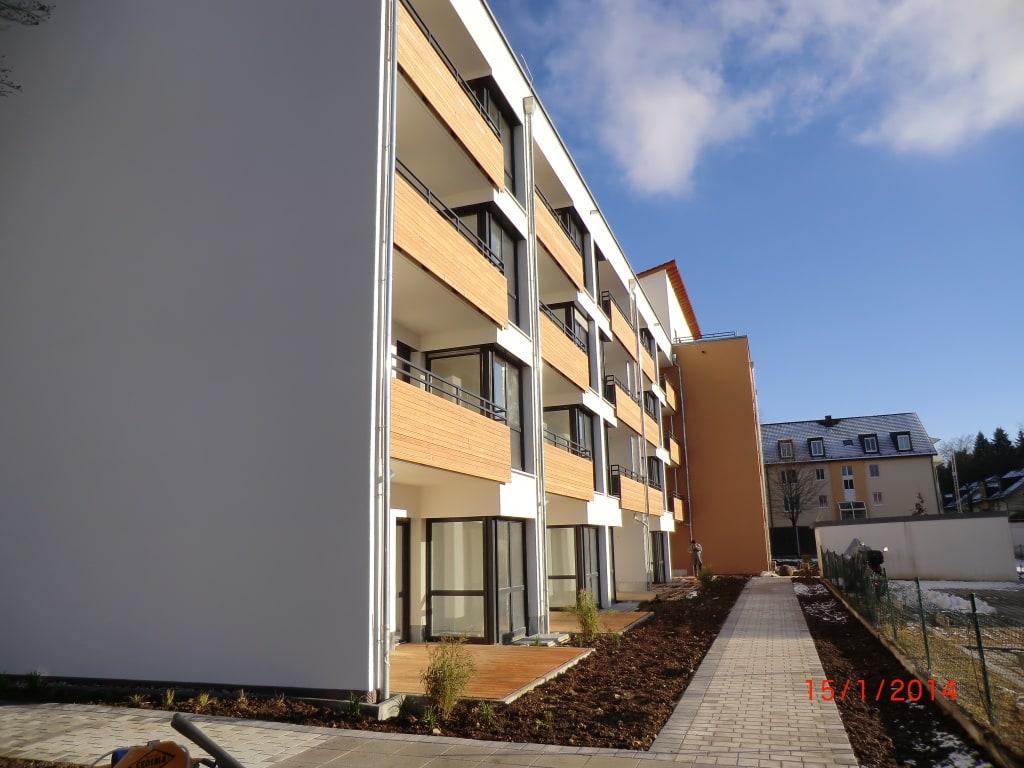 Holzverkleidete Balkone und helle Fassadenfarben lassen den Neubau des Service-Wohnen in Geretsried erstrahlen