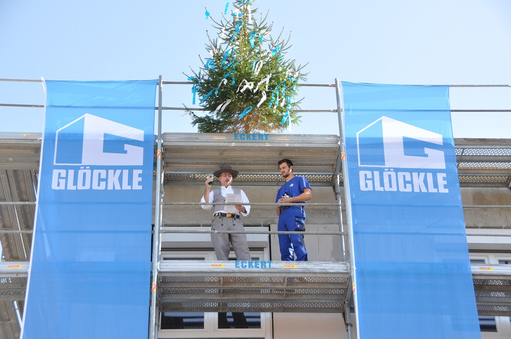 Unter dem geschmückten Richtbaum sprechen die beiden Glöckle-Poliere den traditionellen Richtspruch und erheben dabei das Weinglas