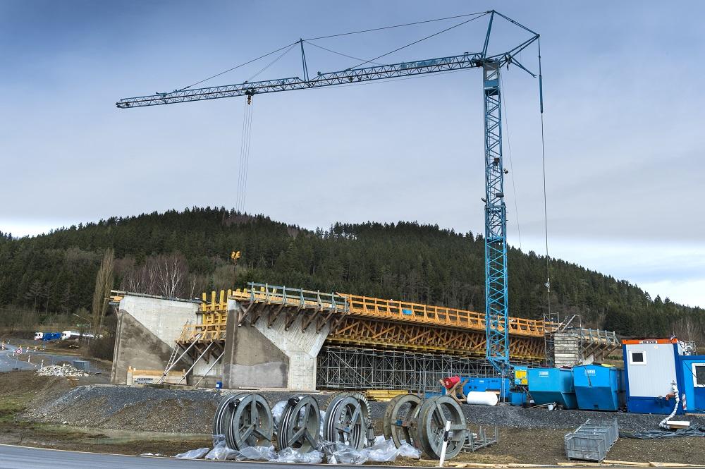 Blauer Glöckle-Baukran ragt hoch über den Brückenneubau in Zeyern