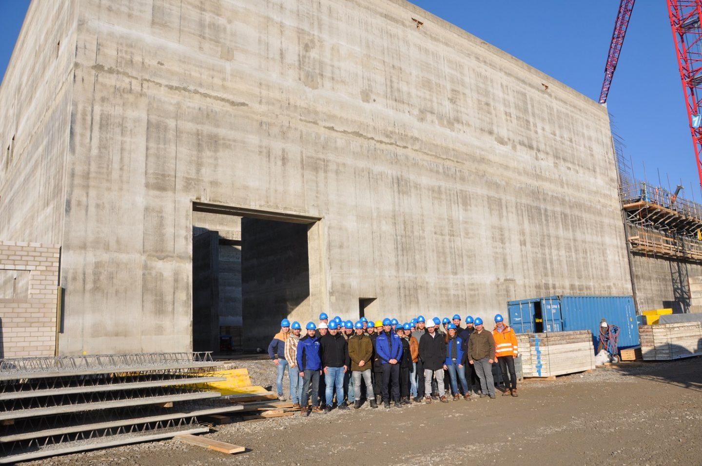 Gruppenbild der Technikerklasse aus Würzburg vor dem Rohbau der neuen Bereitstellungshalle in Grafenrheinfeld