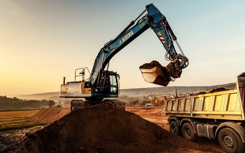 Großer Glöckle-Bagger schaufelt Erde auf einen LKW zum Abtransport