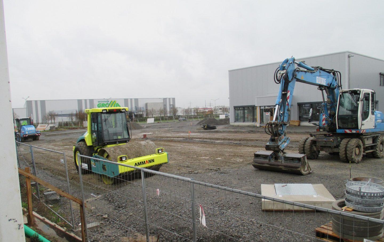 Bagger und Walzen begradigen die neuen Außenflächen rund um einen Neubau