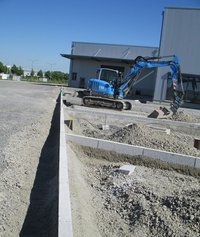 Glöckle-Minibagger schüttet Kies für die neuen Parkflächen des Neubaus von der Firma Beutlhauser in Schweinfurt auf